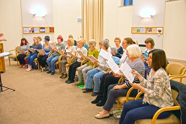 The choir rehearsing a new piece from copies